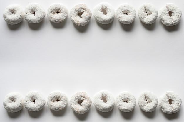 Überkopfaufnahme einer weißen oberfläche mit donuts auf dem oberen und unteren hintergrund