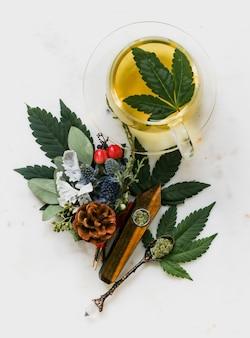 Überkopfaufnahme eines grünen jasmintees mit marihuana-kräutern