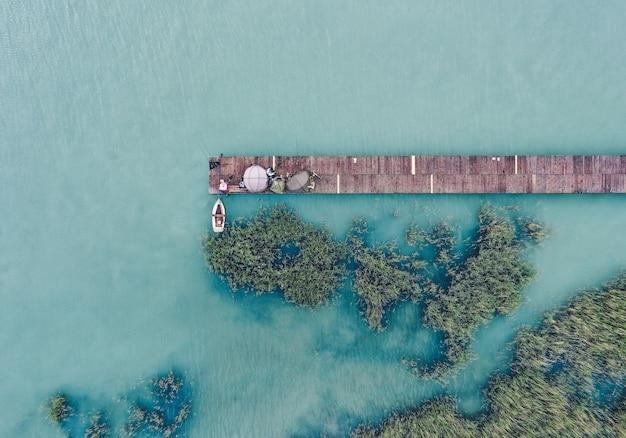 Überkopfaufnahme eines hölzernen docks an der küste mit einem fischerboot daneben