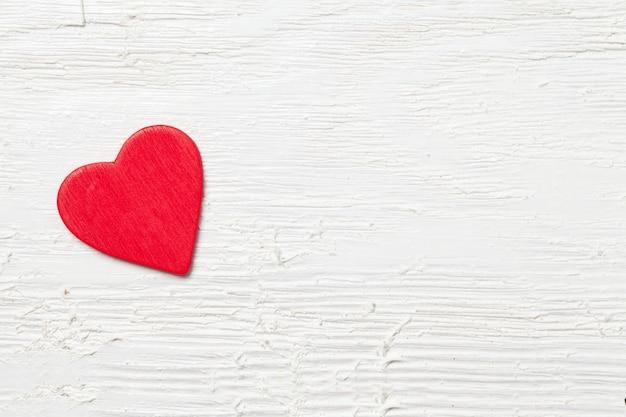Überkopfaufnahme eines kleinen roten herzens auf einem weißen hölzernen hintergrund - romantisches konzept