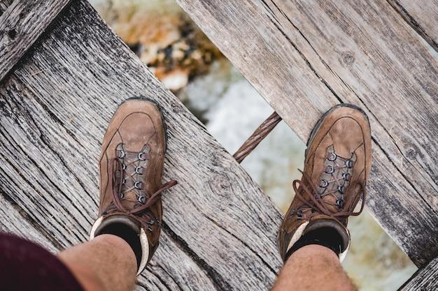 Überkopfaufnahme eines männlichen fußes, der auf einer holzbrücke steht, die wanderschuhe trägt