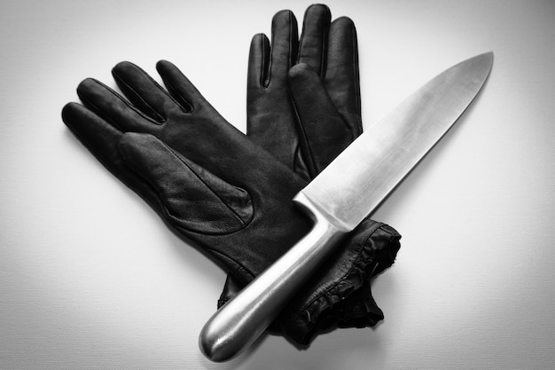 Überkopfaufnahme eines metallmessers über schwarzen handschuhen auf einer weißen oberfläche