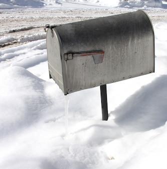 Überkopfaufnahme eines silbernen briefkastens mit schnee in der oberfläche während des winters