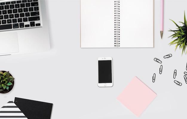 Überkopfaufnahme eines smartphones auf einem weißen schreibtisch mit einem notizbuch, rosa haftnotizen und büroklammern