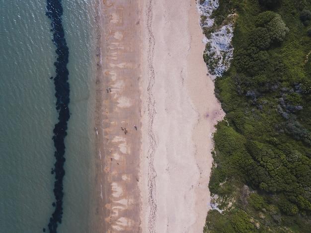 Überkopfaufnahme eines strandes und eines meeres nahe bowleaze cove in weymouth, großbritannien