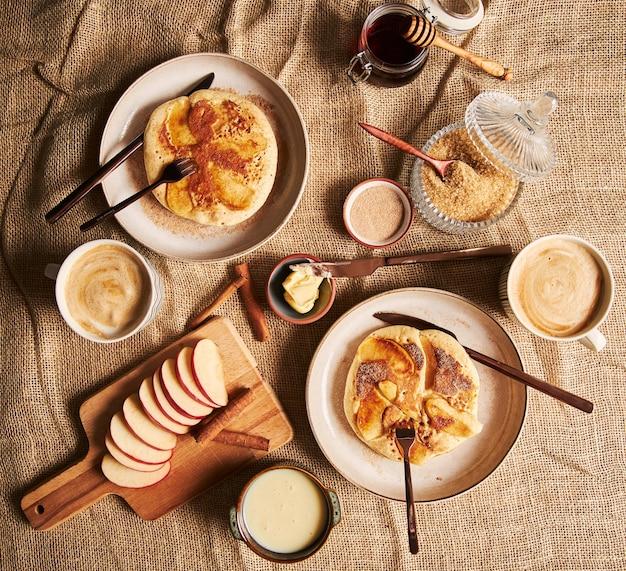 Überkopfaufnahme von apfelpfannkuchen, kaffee, äpfeln, honig und anderen kochzutaten auf der seite