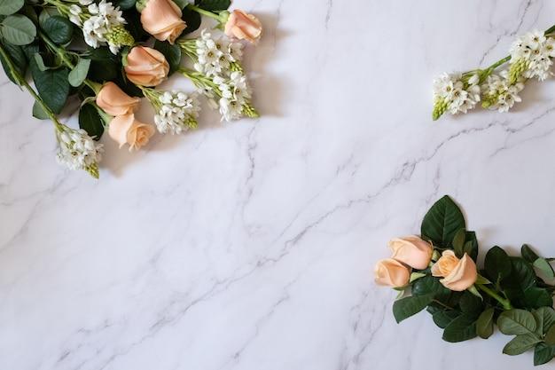 Überkopfaufnahme von gartenrosen mit grünen blättern und weißen kleinen blumen auf einer weißen marmoroberfläche