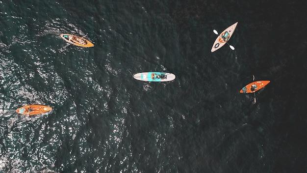 Überkopfaufnahme von menschen in kleinen ruderbooten im wasser