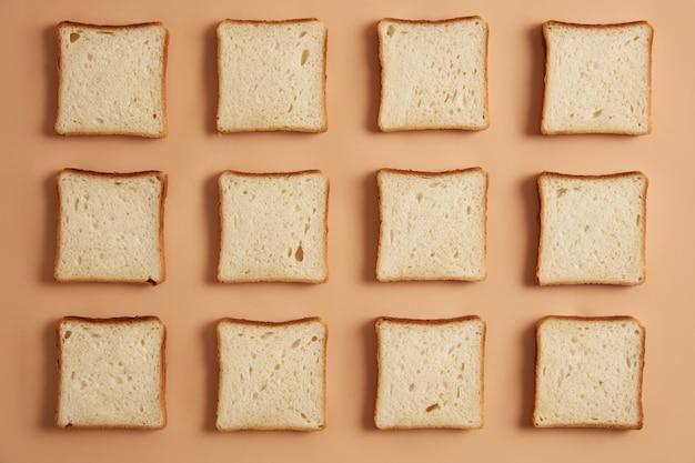 Überkopfaufnahme von ungerösteten brotscheiben, die in reihen angeordnet sind, bereit zum toasten, lokalisiert auf beigem studiohintergrund. leckeres sandwich zubereiten. leckerer snack. geschnittenes backprodukt. flach liegen.