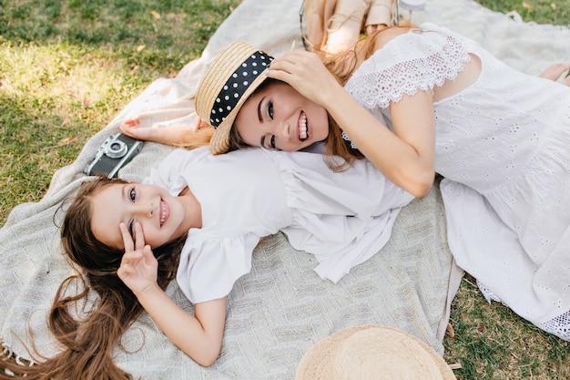 Überkopfporträt der entspannenden mädchen, die auf decke liegen und lächeln. aufgeregte junge frau, die auf dem gras ruht, das mit freudiger tochter spielt.