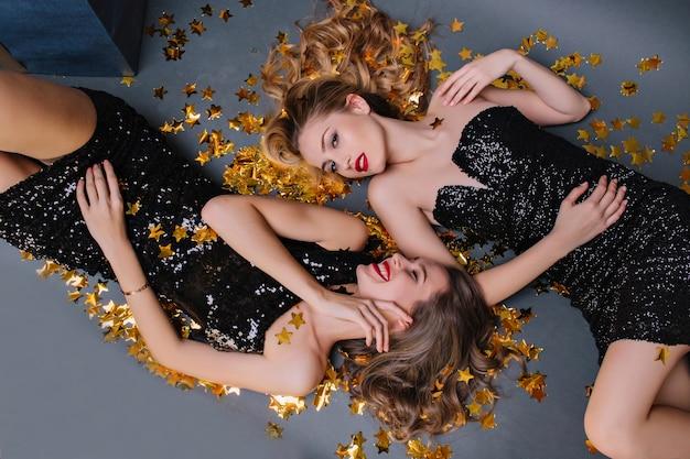Überkopfporträt der entzückenden blassen frau, die auf dem boden liegt und freundin mit lächeln betrachtet. glamouröse mädchen genießen party und entspannen sich auf funkelnden konfetti.