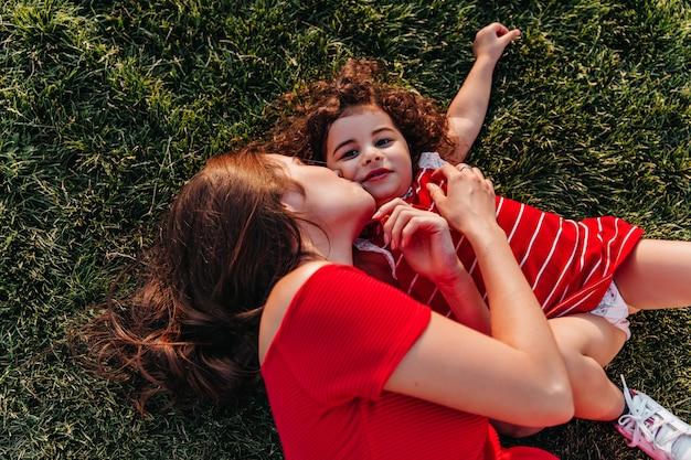Überkopfporträt der glücklichen familie, die zusammen im sommertag kühlt. außenaufnahme der dunkelhaarigen frau, die ihre kleine tochter küsst, während sie auf dem gras liegt.
