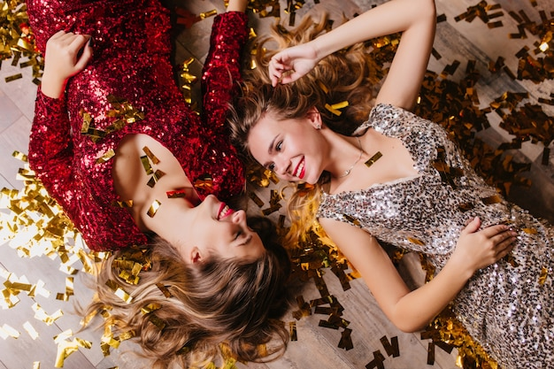 Überkopfporträt der inspirierten frauen trägt funkelnde kleidung niedliches lächeln, während sie sich nach neujahrsparty ausruht