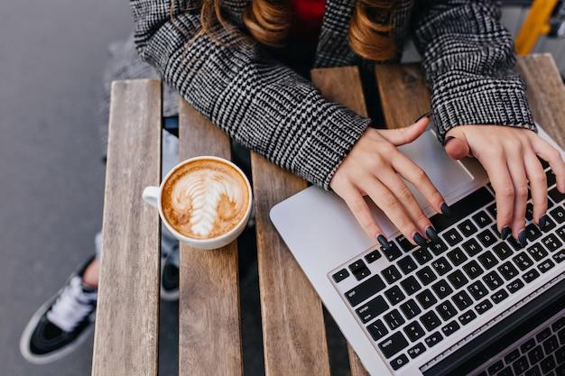 Überkopfporträt der stilvollen frau im grauen mantel, der am holztisch mit laptop sitzt