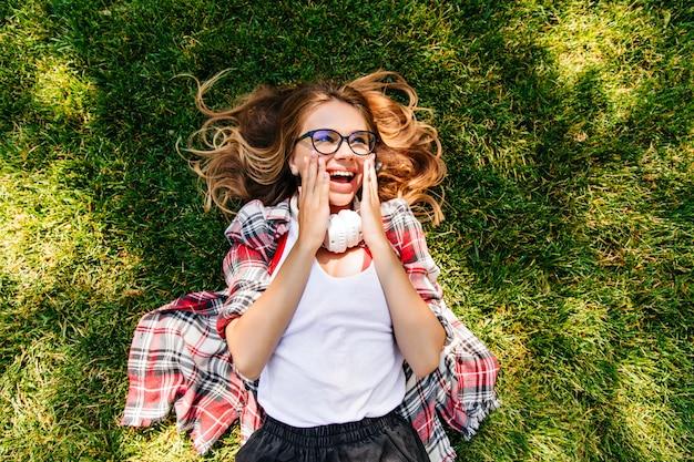 Überkopfporträt des frohen kaukasischen mädchens, das auf gras liegt. entspannte entzückende dame, die im sommertag chillt.