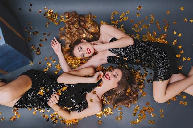 Überkopfporträt von zwei freudigen mädchen, die auf goldenem konfetti liegen. langhaarige dame im schwarzen kleid, die spaß mit der brünetten schwester auf neujahrsparty hat.