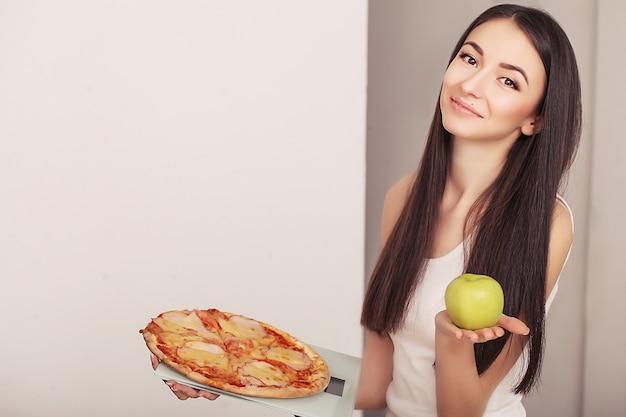 Überladene frau, die auf der waage hält pizza steht.