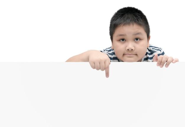 Überladener fetter junge, der auf die weiße fahne - lokalisiert auf weißem hintergrund mit kopienraum für eingangstext zeigt