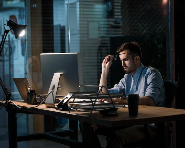 Überladener mann, der spät im büro arbeitet