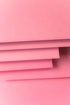 Überlagert vom rosafarbenen farbigen kartenpapierhintergrund