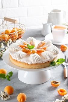 Überlagerter käsekuchen mit aprikose auf tortenständer, heller hintergrund. früchtekuchen. französisches gebäck.