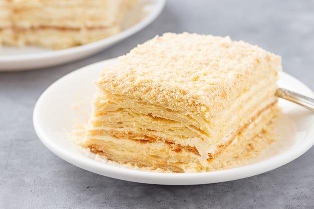 Überlagerter kuchen mit sahne napoleon millefeuille vanillescheibe auf einem weißen teller.