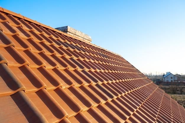 Überlappende reihen von gelben keramischen dachziegeln, die auf holzbrettern montiert sind, die das dach des wohngebäudes im bau bedecken.