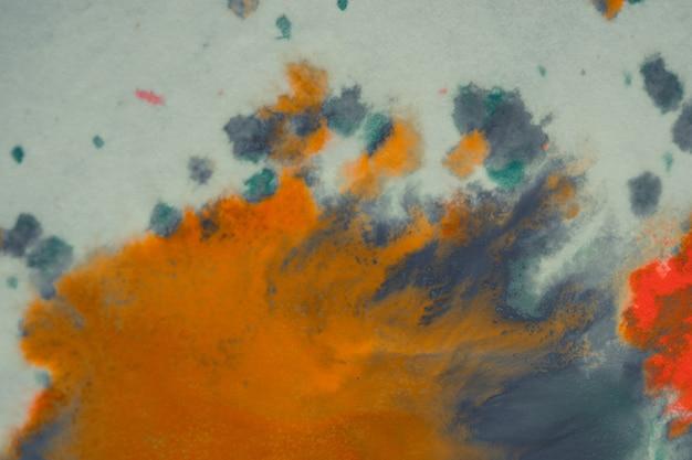 Überlaufende leuchtend orange und dunkelblaue farbe auf papier. abstrakter verblasster hintergrund im schäbigen stil. mischen von farben nahaufnahme. abstrakter basishintergrund abstrakter hintergrundhintergrundrahmen für kreativitätskunst