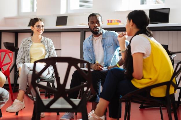 Überlegen. nervöser junger mann, der die freundlichen jungen mädchen ansieht, während er neben ihnen sitzt und über sein persönliches problem nachdenkt
