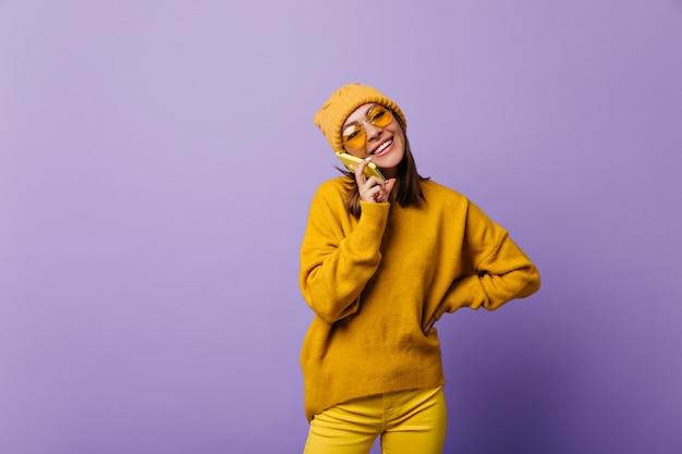 Überlegenes wundervolles aktives mädchen im gelben gesamtblick, das durch ihr telefon mit fröhlicher stimmung spricht. porträt des 24-jahres-modells
