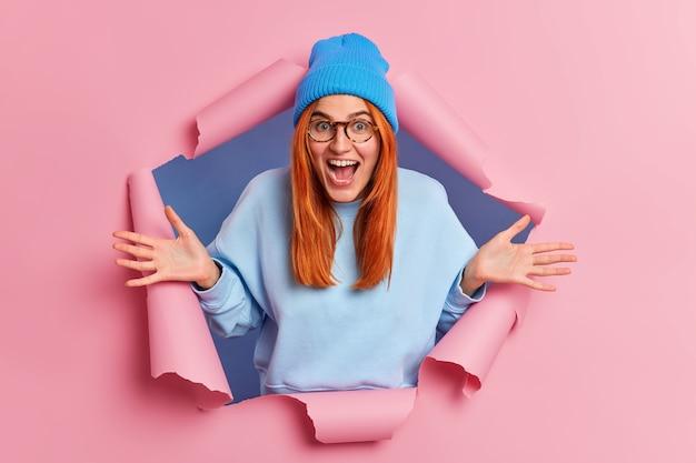 Übermotiv positive ingwer junge frau ruft laut spreizt handflächen fühlt sich sehr froh trägt blauen hut und pullover bricht durch rosa papier