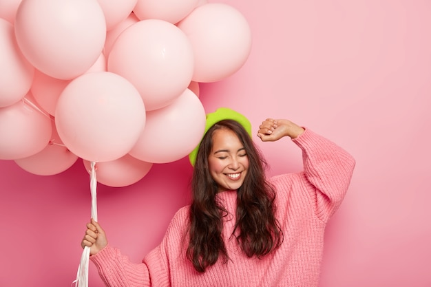 Übermotivierende frau mit fröhlichem gesichtsausdruck, hebt die hand, tanzt zur musik, hat spaß auf der party, hält luftballons, hat gute laune während ihres geburtstages