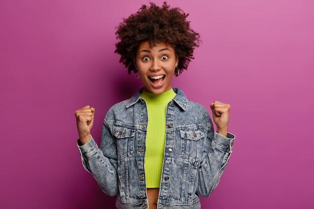 Übermotivierende triumphierende frau mit afro-frisur, lächelt und wird gewinnerin oder champion
