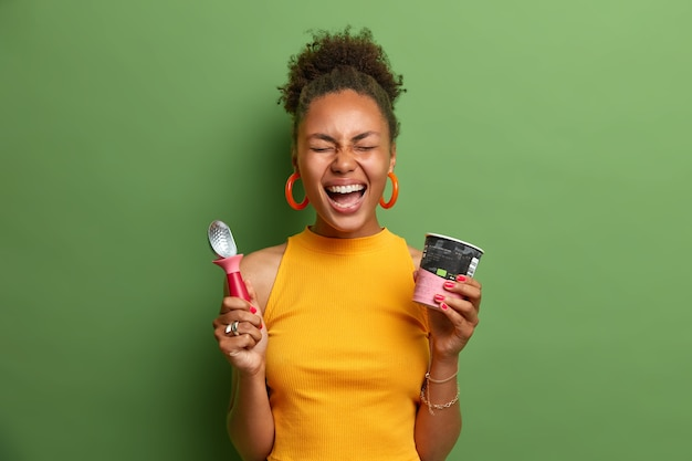 Übermotivierte fröhliche dunkelhäutige teenagerin lacht laut, hat spaß und isst köstliches gefrorenes dessert, hält eine tasse eis und einen löffel, gekleidet in leuchtend gelbe kleidung, drückt glück aus