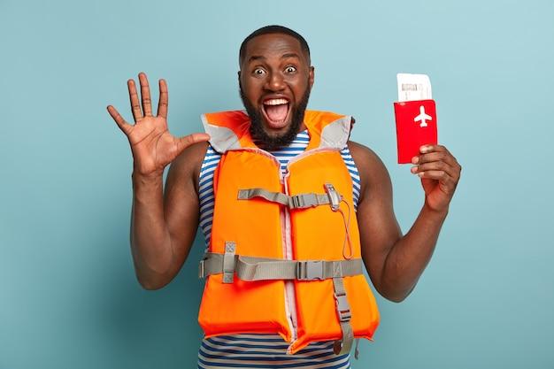 Übermotivierter dunkelhäutiger mann schreit emotional, hält die handfläche hoch, reagiert auf unerwartete reisen, hält den pass mit tickets, trägt eine schwimmweste. menschen