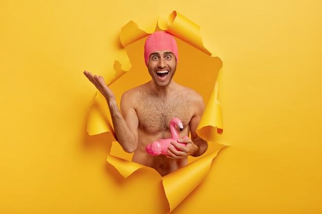 Übermotivierter kaukasischer mann hebt die hand, fühlt sich zufrieden, hält schwimmring in form eines flamingos, genießt die sommerzeit