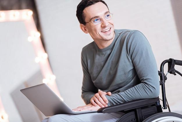 Übermütig. hübsche männliche person, die hände zusammenhält und laptop auf den knien hält, während sie zur seite schaut