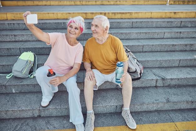 Übermütige, attraktive ältere frau, die sich und ihren zufriedenen grauhaarigen kaukasischen ehemann auf der treppe fotografiert