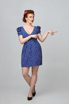 Überprüfen sie dies heraus. attraktive wunderschöne junge europäische frau mit kurvigem, perfektem körper, der in stilvollen retro-kleidern posiert, mit erstauntem ausdruck, zeigefinger auf copyspace-wand zeigend