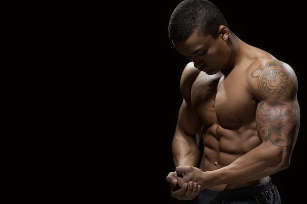 Überprüfen sie diesen körper! junger hübscher afrikanischer mann mit atemberaubendem zerrissenem körper, der sein perfektes sixpack zeigt