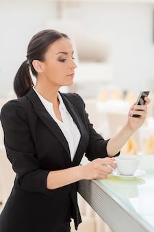 Überprüfen von geschäftsnachrichten. selbstbewusste junge frau in abendkleidung, die kaffee trinkt und auf ihr handy schaut, während sie sich an der bartheke lehnt