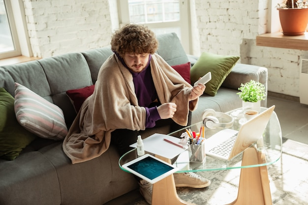 Überprüfen von grafiken. mann, der während der quarantäne von coronavirus oder covid-19 von zu hause aus arbeitet, remote-office-konzept. junger geschäftsmann, manager, der aufgaben mit smartphone, laptop, tablet erledigt, hat online-konferenz.