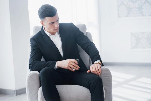 Überprüft die zeit auf einer luxusuhr. junger eleganter kerl im schwarzen anzug sitzt auf weißem stuhl und hält glas mit alkohol.