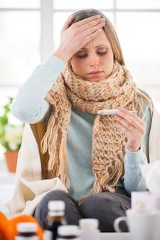Überprüfung der körpertemperatur. junge frau mit plaid bedeckt, die ihre körpertemperatur überprüft, während sie in ihrer wohnung im bett sitzt Premium Fotos