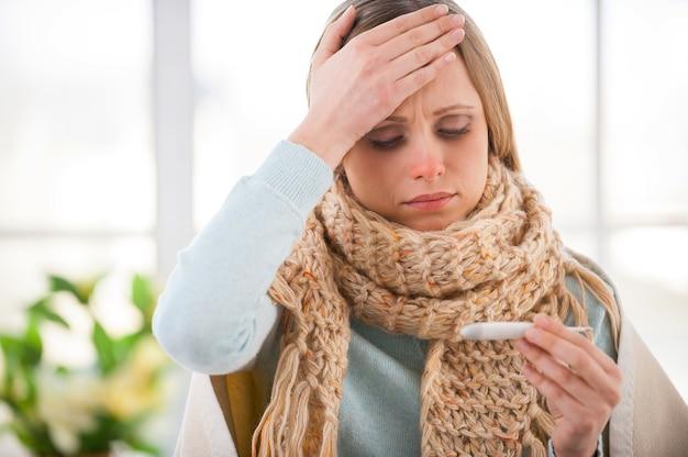 Überprüfung der körpertemperatur. junge frau mit plaid bedeckt, die ihre körpertemperatur überprüft, während sie in ihrer wohnung im bett sitzt