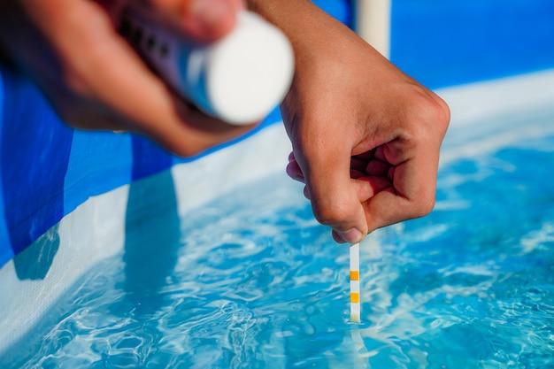 Überprüfung der wasserqualität eines pools mit hilfe eines teststreifens mit ph-wert chlor und algizid