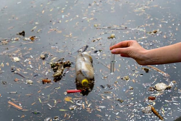 Überprüfung der wasserqualität im abwasser. reagenzglas mit einer probe in der hand. abwasserbehandlung