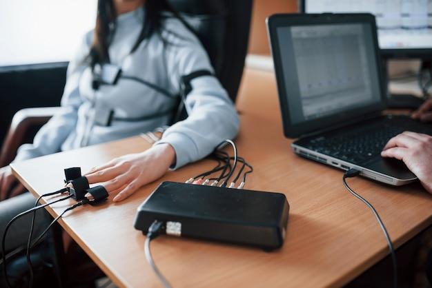 Überprüfung der wiedergabetreue. mädchen geht lügendetektor im büro vorbei. fragen stellen. polygraphentest