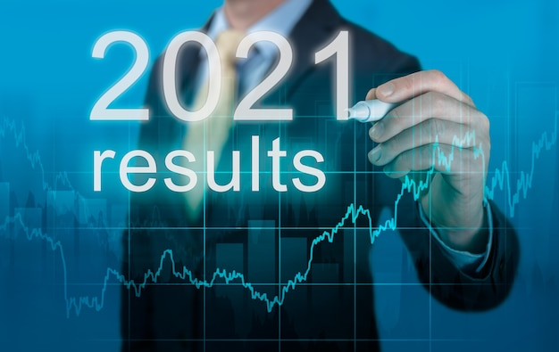 Überprüfung der wirtschaftsergebnisse 2021. geschäftsmann schreibt ergebnisse 2021 auf virtuellen bildschirm. letzten jahresrückblick im geschäft. wirtschaftsindikatoren, krisenbewältigung und wirtschaftliche erholung nach der coronavirus-pandemie