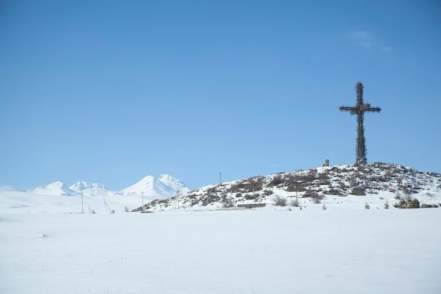 Überqueren sie auf eisigem berg in der wintersaison unter himmel